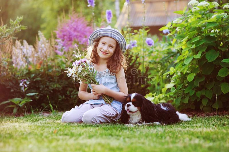 Happy child girl relaxing in summer garden with her spaniel dog. Wearing gardener hat and holding bouquet of flowers. Blooming perennials on background stock photography