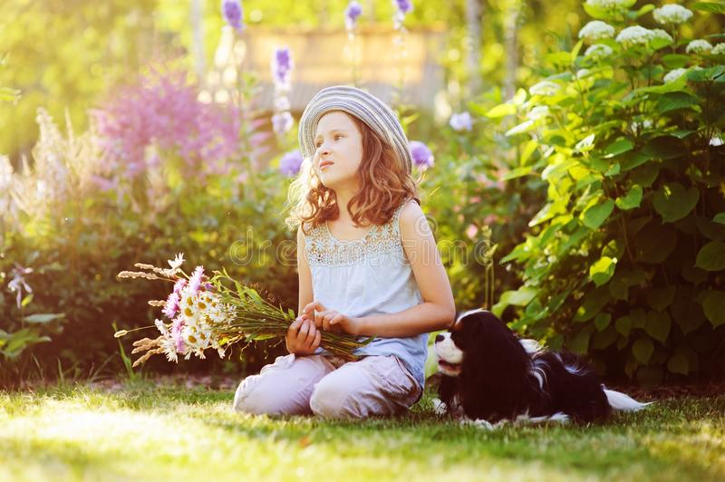 Happy child girl relaxing in summer garden with her spaniel dog, wearing gardener hat and holding bouquet. Of flowers. Blooming perennials on background royalty free stock photography