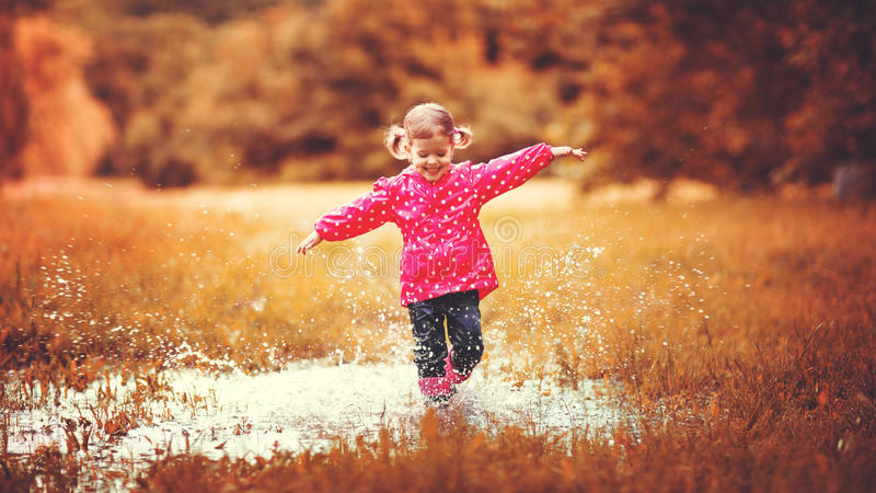 Happy child girl running and jumping in puddles after rain. In autumn stock photography