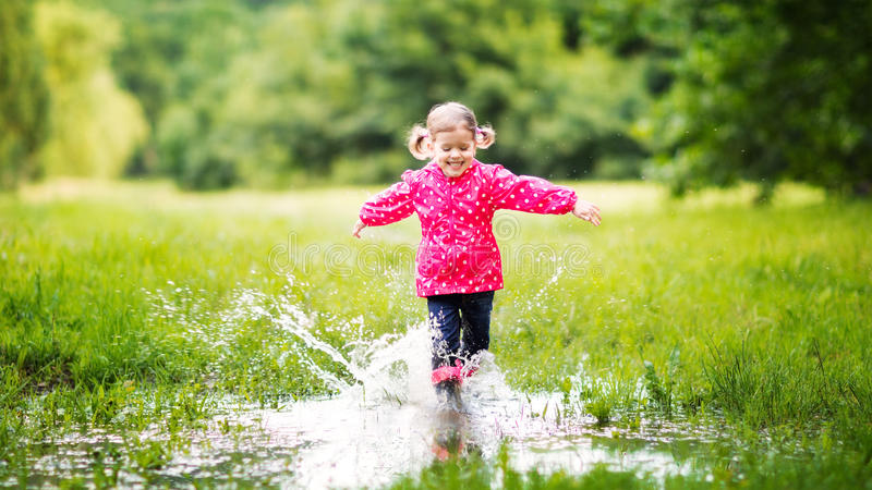 Happy child girl running and jumping in puddles after rain. In summer stock photos