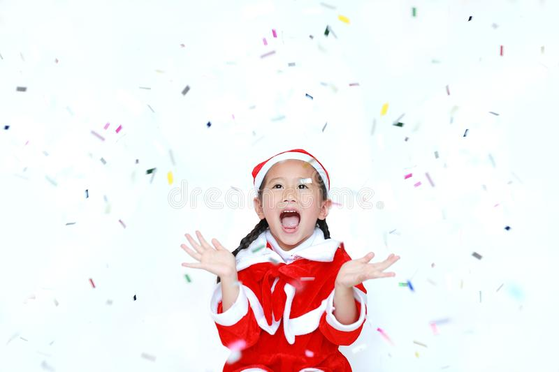 Happy child girl in Santa costume dress with colorful confetti o. N white background. Merry Christmas and Happy New Year Concept royalty free stock photos