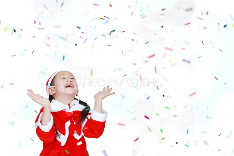 Happy child girl in Santa costume dress with colorful confetti ribbon paper thrown on white background. Merry Christmas and Happy royalty free stock photo
