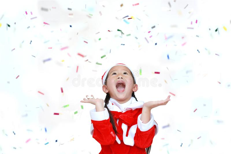 Happy child girl in Santa costume dress with colorful confetti ribbon paper thrown on white background. Merry Christmas and Happy. New Year Concept stock photo