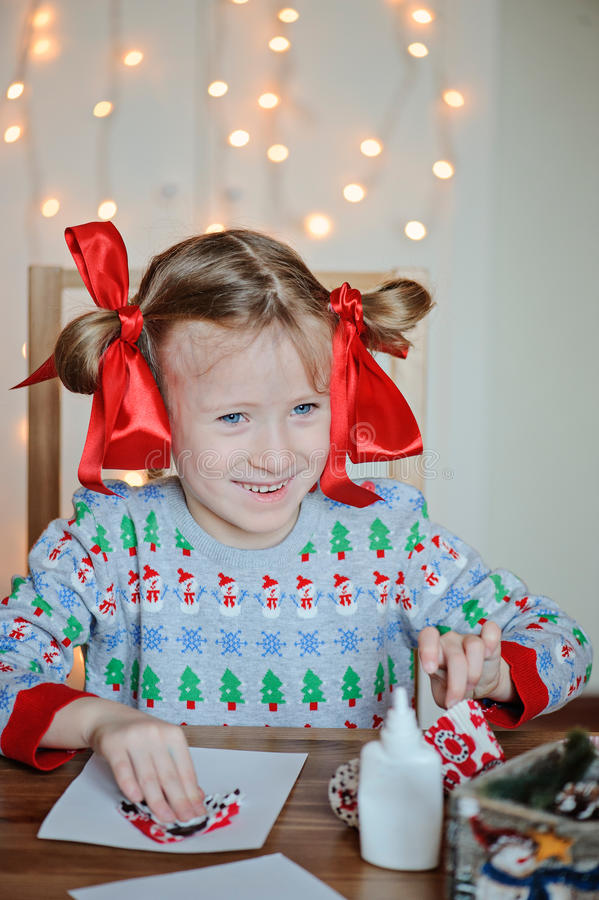 Happy child girl in seasonal sweater making Christmas post cards. With light on background stock image