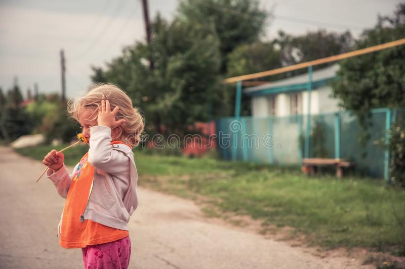 Happy child girl smell flower dandelion  in summer countryside with copy space concept happy carefree childhood lifestyle royalty free stock photo