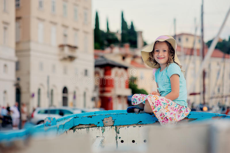 Happy child girl in straw on summer vacation in Piran, Slovenia, sitting on boat with city view on background stock images