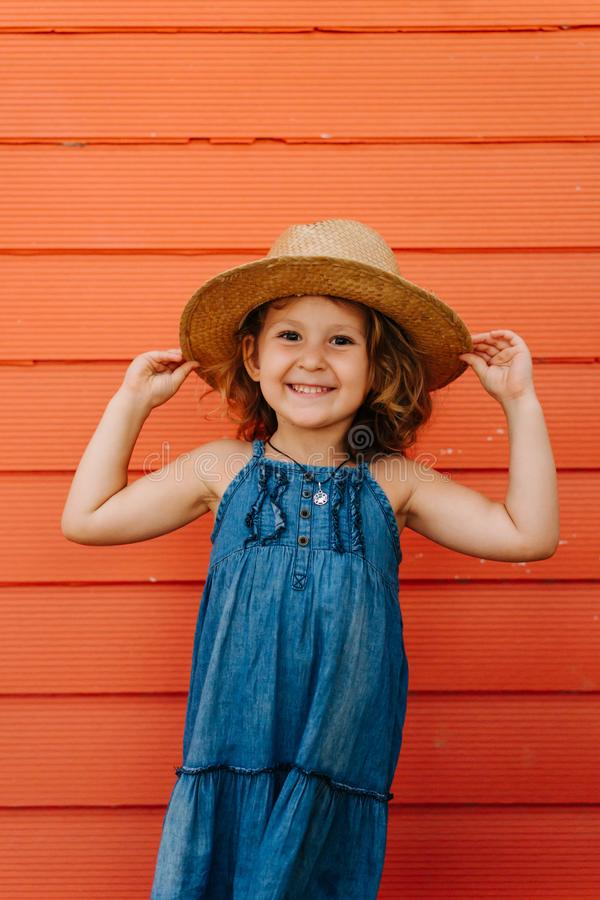 Happy child girl in summer hat and a beautiful blue dress against orange wall royalty free stock photo
