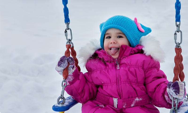 Happy child girl on swing in sunset winter. Little kid playing on a winter walk in nature stock images