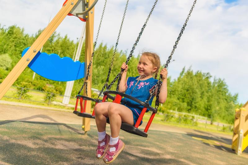 Happy child girl on swing on warm and sunny day outdoors. Little kid playing on nature walk in playground in park, cute blond girl royalty free stock image