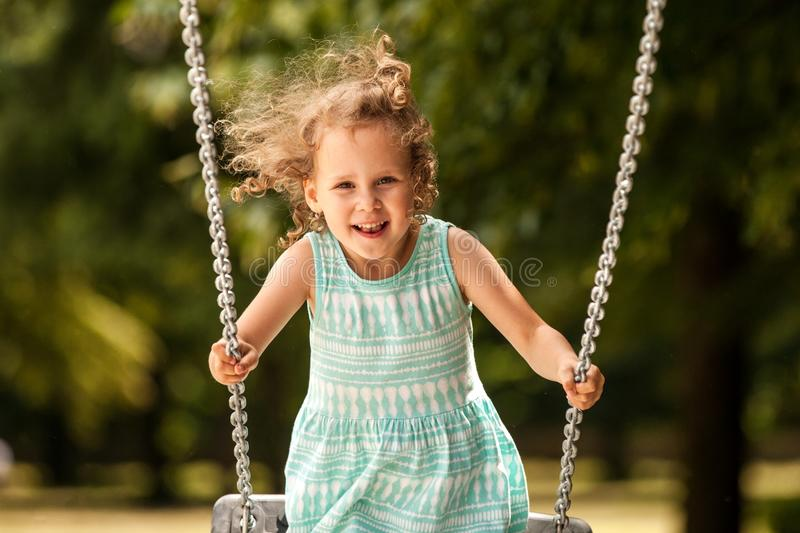 Happy child girl on swing on warm and sunny day outdoors. Little kid playing on nature walk in playground in park, cute blond girl stock photos