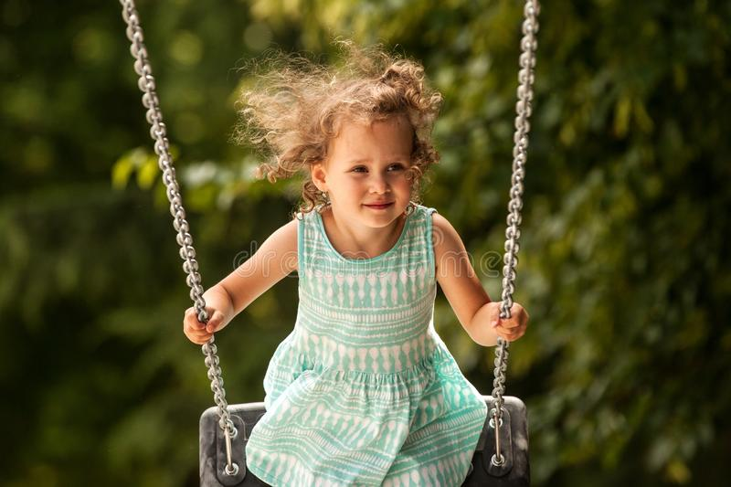 Happy child girl on swing on warm and sunny day outdoors. Little kid playing on nature walk in playground in park, cute blond girl royalty free stock images