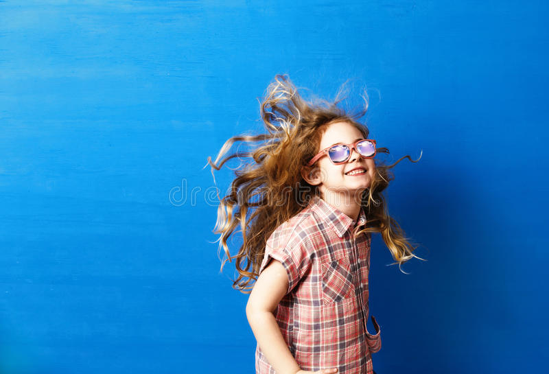 Happy child girl tourist in pink sunglasses at the blue wall. Travel and adventure concept royalty free stock photography