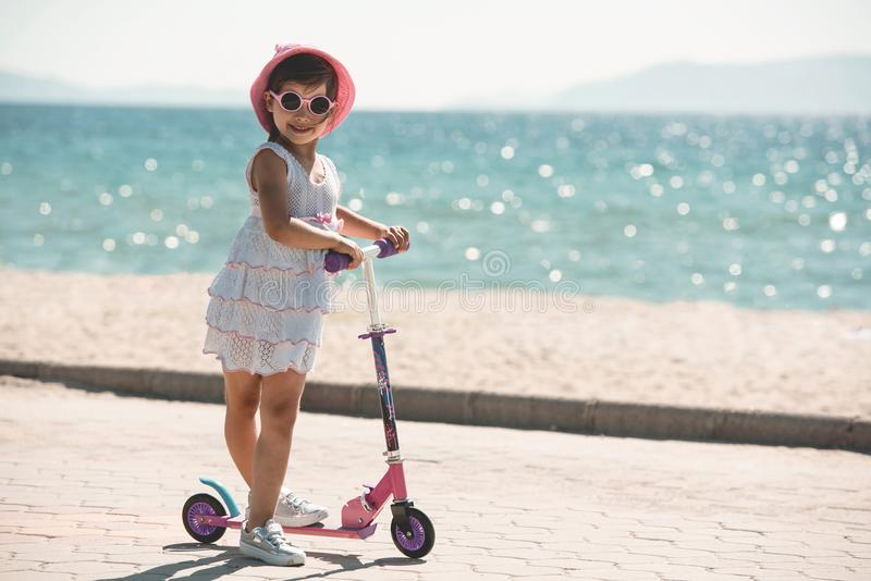 Happy Child Girl Tourist Riding Scooter At Seaside royalty free stock photos