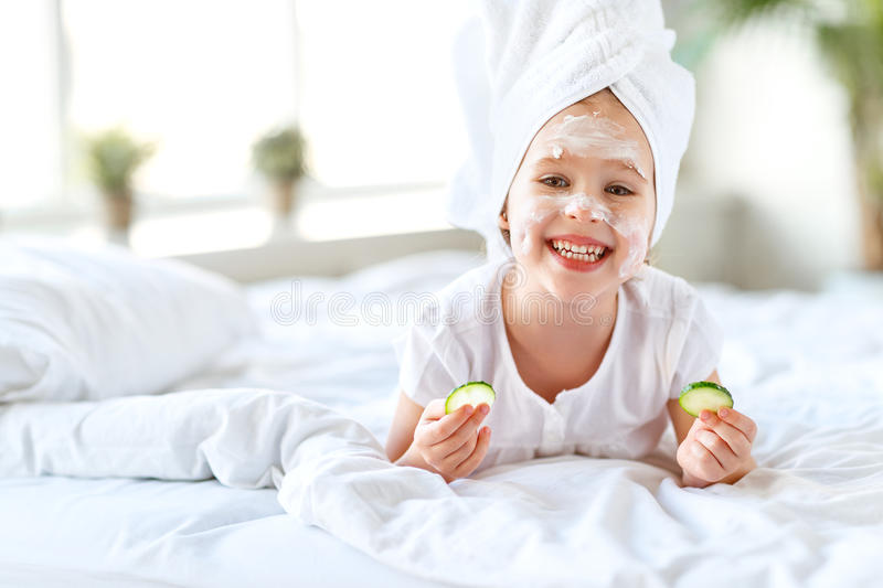 Happy child girl in towel with mask on face stock image