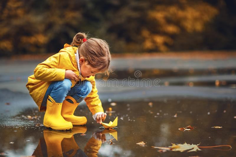 Happy child girl with umbrella and paper boat in puddle in a stock photo