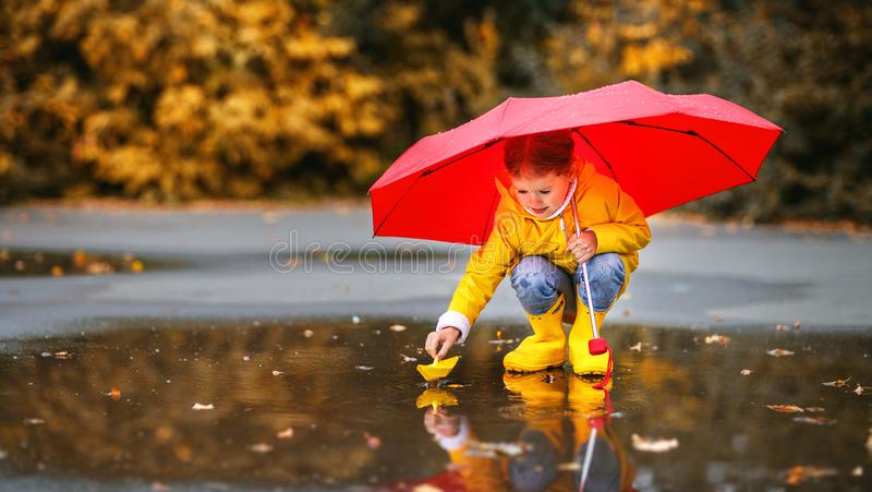 Happy child girl with umbrella and paper boat in puddle in a royalty free stock photos