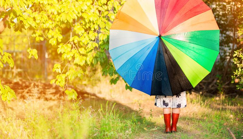 Happy child girl walk with multicolored umbrella under rain. Happy child girl walk with multicolored umbrella under autumn rain royalty free stock images