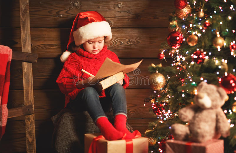 Happy child girl writes letter to Santa Claus at the Christmas t stock photo