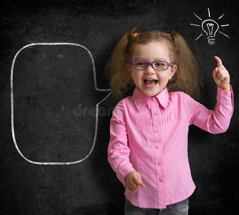 Happy child in glasses standing near school chalkboard with bulb stock photos
