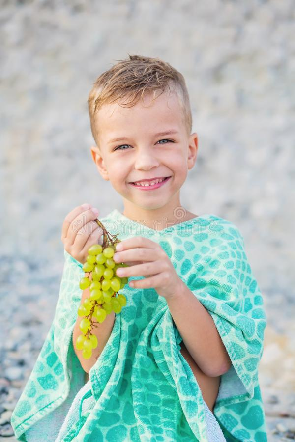 Happy child with grapes on vacation wrapped stock photo