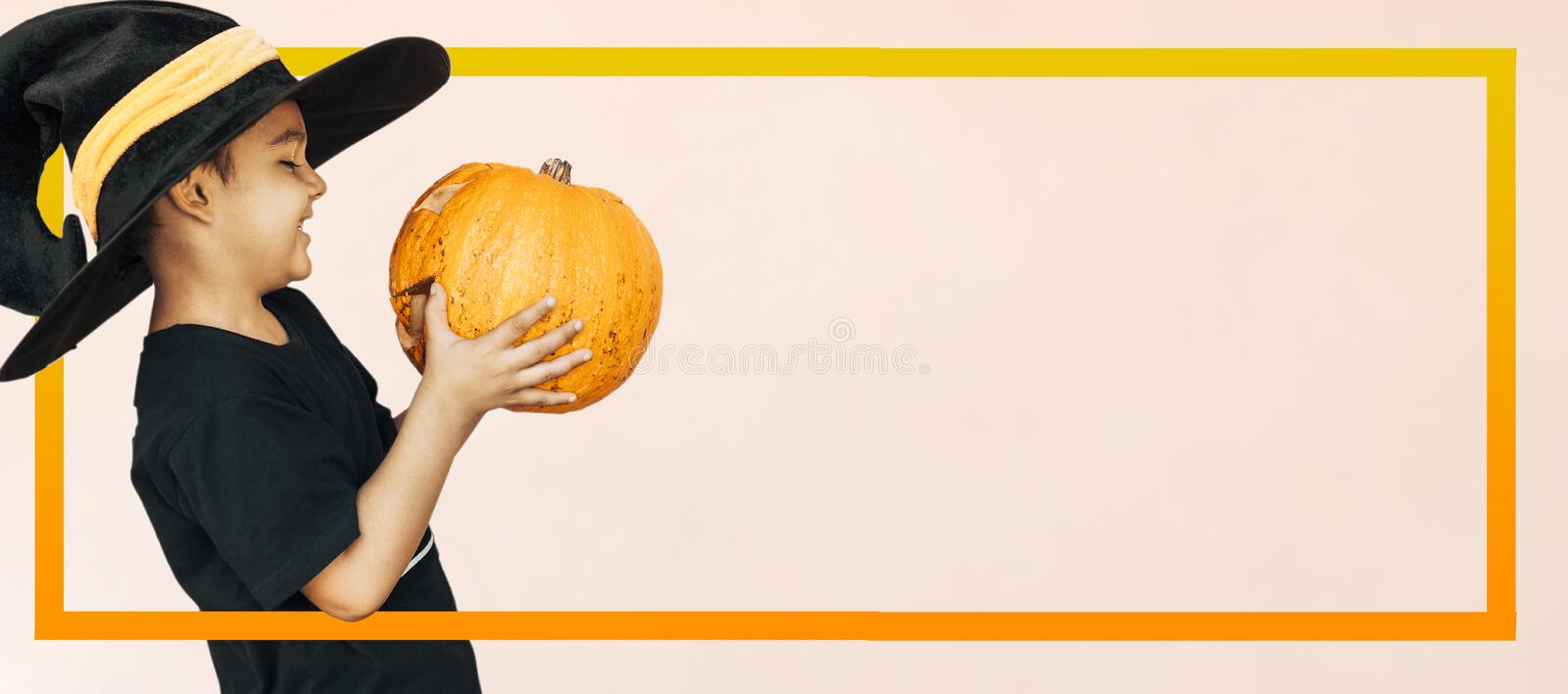 Happy child with Halloween jack o lantern pumpkin. Halloween 2019 holiday concept. Cute little kid with carved pumpkin. Happy little boy holding a big Halloween royalty free stock photography