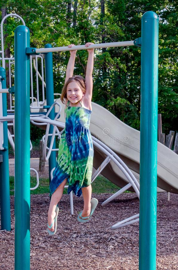 Happy child hanging from monkey bars stock images
