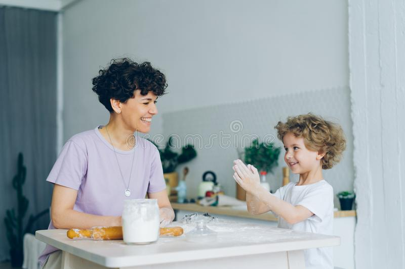 Happy child having fun with flour clapping hands cooking pastry with mom at home stock images