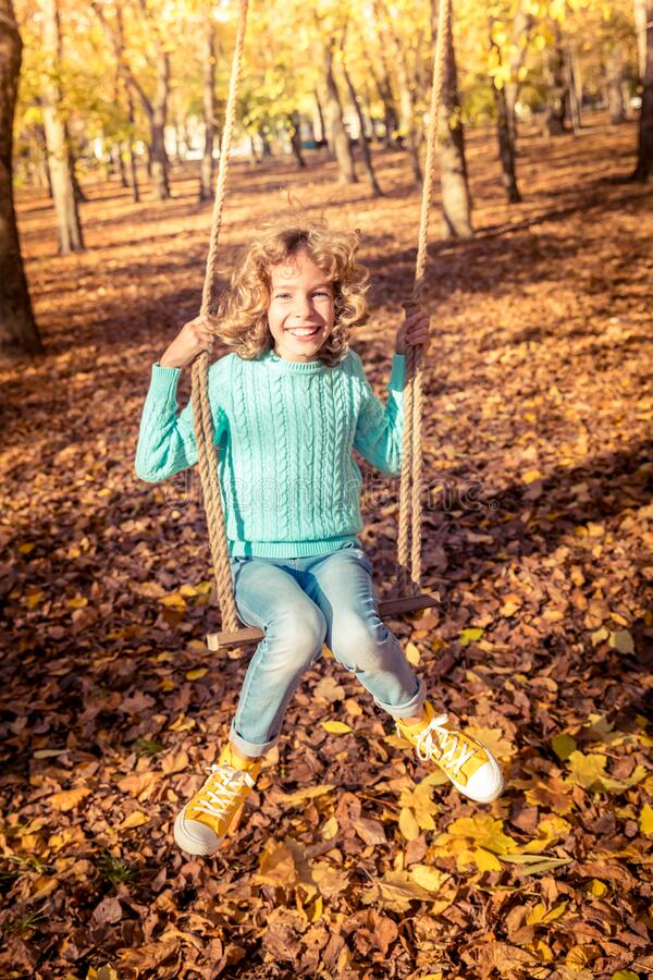 Happy child having fun outdoor in autumn park royalty free stock photography