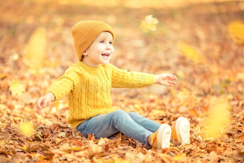 Happy child having fun outdoor in autumn park stock photography