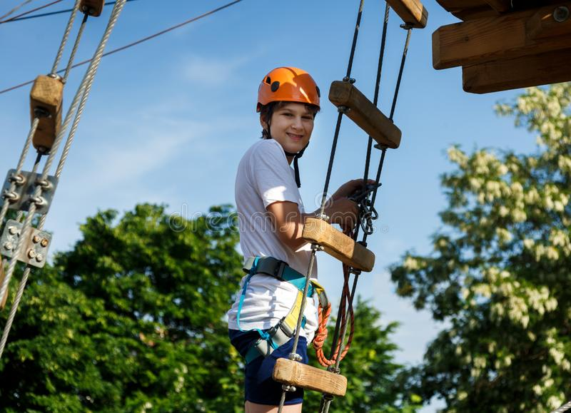 Happy child, healthy teenager school boy in orange helmet enjoys activity in a climbing adventure rope park stock images