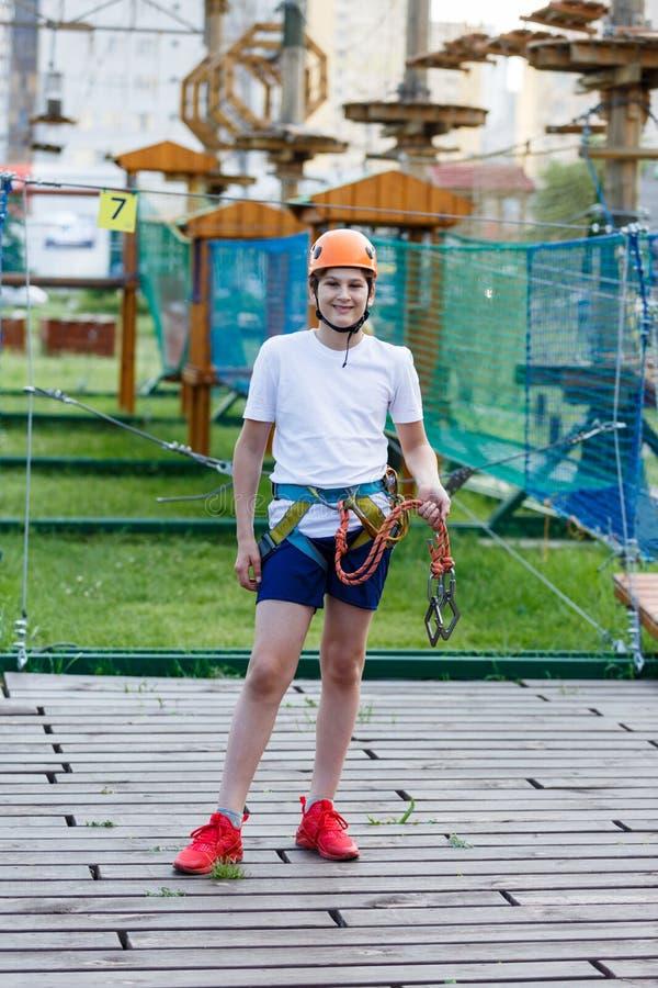Happy child, healthy teenager school boy in orange helmet enjoys activity in a climbing adventure rope park stock photography