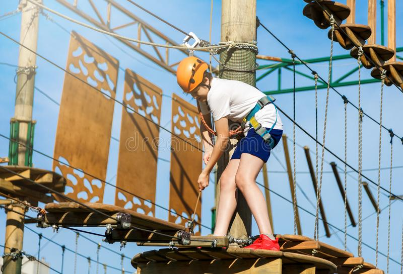 Happy child, healthy teenager school boy in orange helmet enjoys activity in a climbing adventure rope park. On a sunny summer day royalty free stock photos