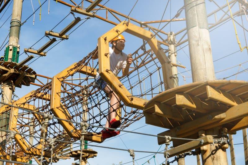 Happy child, healthy teenager school boy in orange helmet enjoys activity in a climbing adventure rope park royalty free stock photography