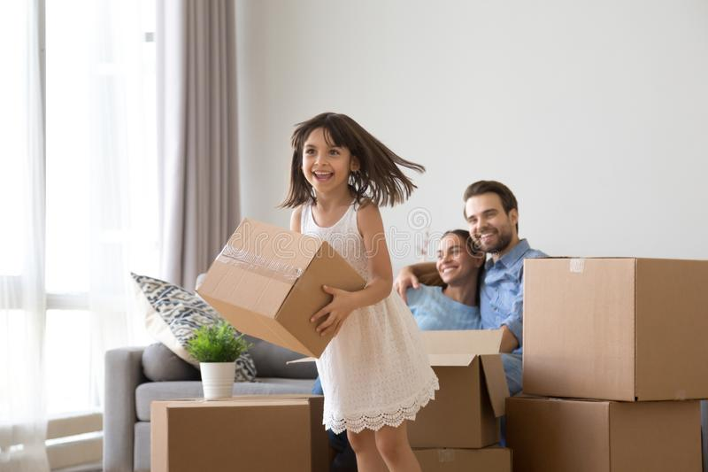 Happy child helps parents with carton boxes at moving day royalty free stock image