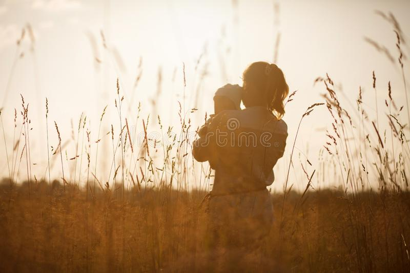 Happy child and his mom have fun outdoors in a field flooded with sunlight royalty free stock photos