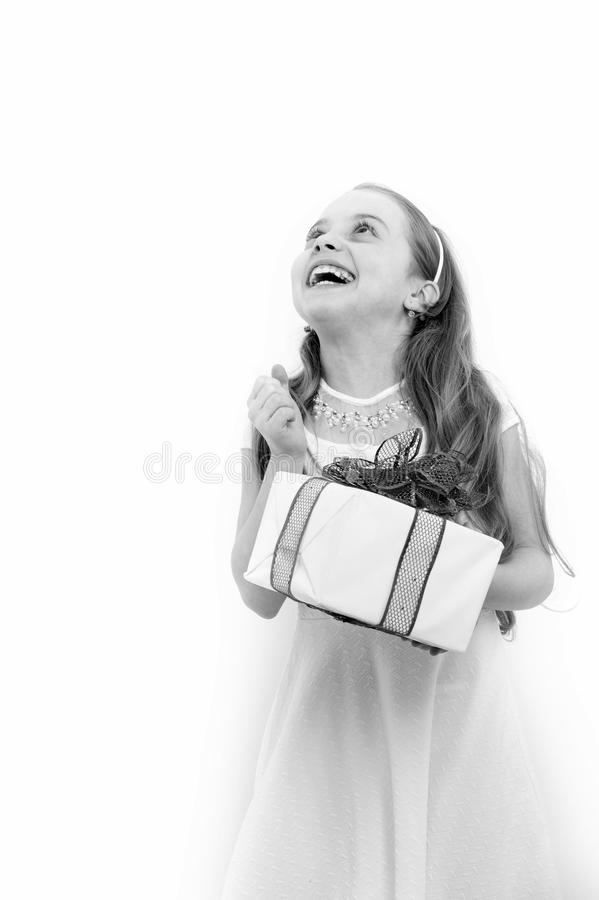 Happy child hold box with red bow. Girl with long blond hair look up isolated on white. Holiday gift, present and surprise. Birthday, anniversary celebration stock photography