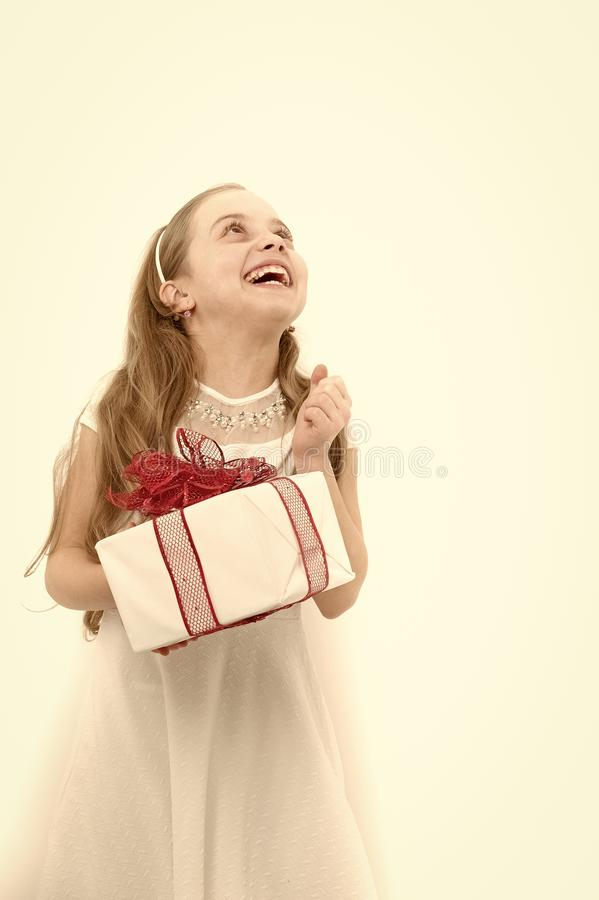 Happy child hold box with red bow. Girl with long blond hair look up isolated on white. Holiday gift, present and surprise. Birthday, anniversary celebration royalty free stock photos