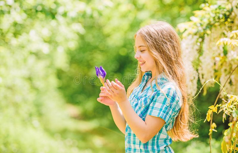 Happy child hold iris flower. Natural beauty. Childhood happiness. summer vacation. Green environment. little girl and stock images