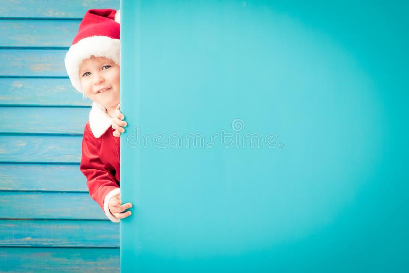 Happy child holding blue Christmas banner blank against wooden background. Happy child holding blue banner blank against wooden background. Christmas greeting royalty free stock photography