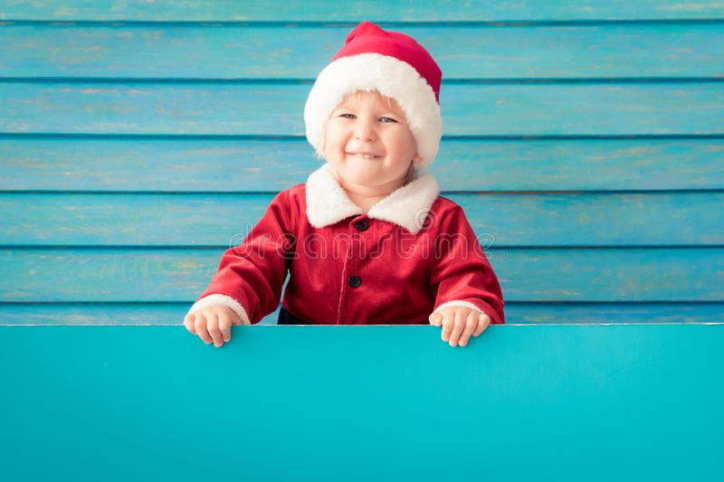 Happy child holding blue Christmas banner blank against wooden background. Happy child holding blue banner blank against wooden background. Christmas greeting royalty free stock photo