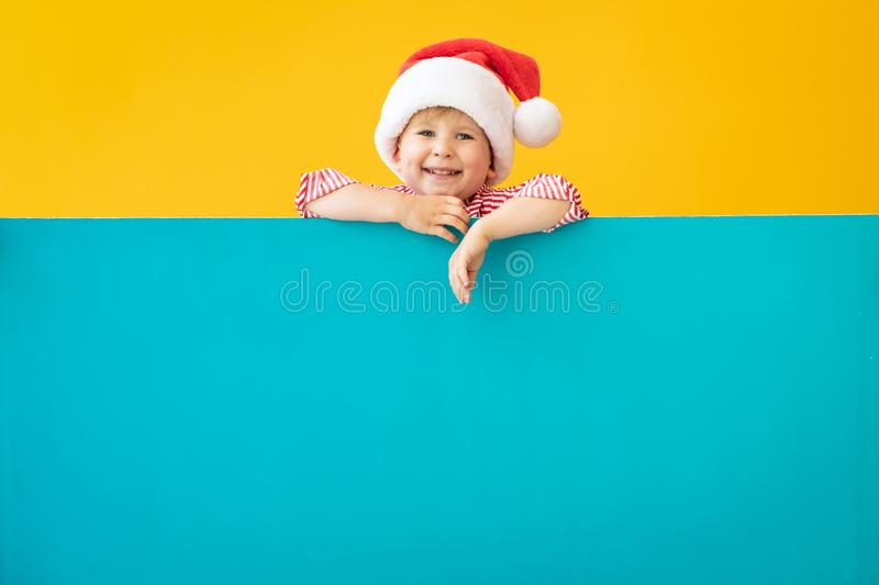 Happy child holding blue Christmas banner blank against yellow background. Happy child holding blue banner blank against yellow background. Christmas greeting stock photos