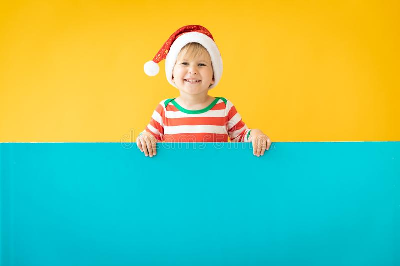Happy child holding blue Christmas banner blank against yellow background. Happy child holding blue banner blank against yellow background. Christmas greeting royalty free stock images