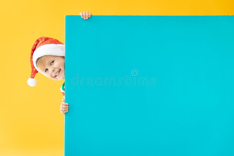 Happy child holding blue Christmas banner blank against yellow background. Happy child holding blue banner blank against yellow background. Christmas greeting stock photo