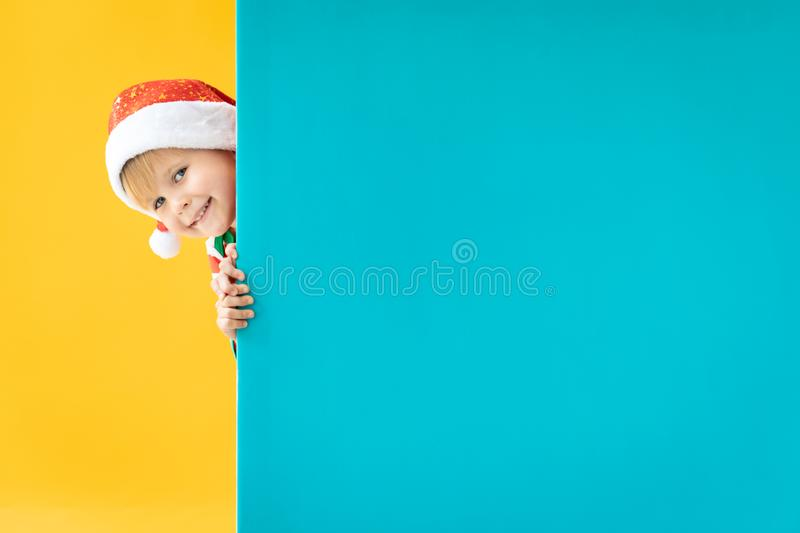 Happy child holding blue Christmas banner blank against yellow background royalty free stock photography