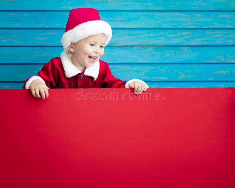 Happy child holding cardboard banner blank. Funny kid holding cardboard banner blank. Child playing at home. Christmas holiday concept. Copy space royalty free stock photos