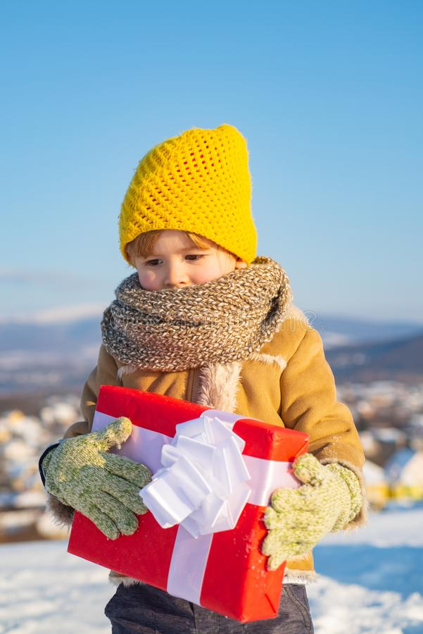 Happy child holding Christmas presents. Christmas holidays. Cute preschooler boy in a knitted yellow hat holding a red. Box with a gift. Beautiful winter nature stock photos