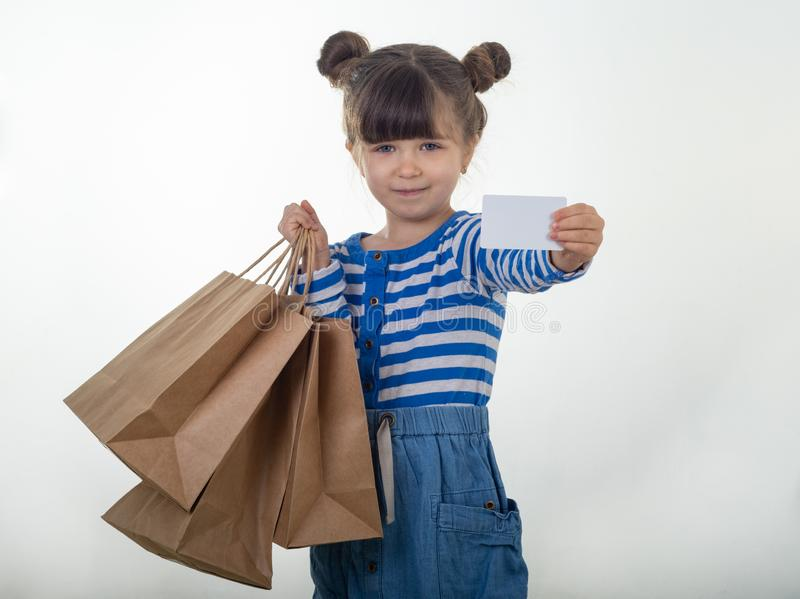 Happy child holding discount white card and shopping bags in her hands. Kid with credit card. stock photos