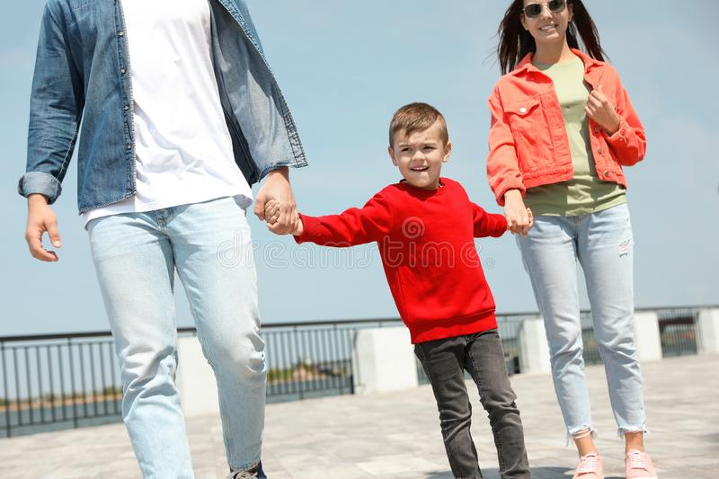 Happy child holding hands with his parents outdoors royalty free stock image