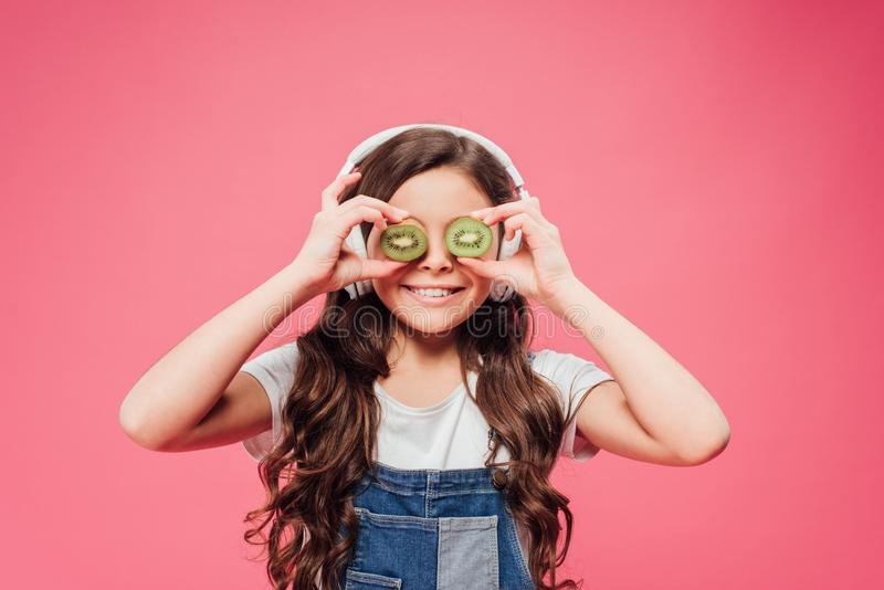 Happy child holding kiwi fruit over eyes isolated royalty free stock image