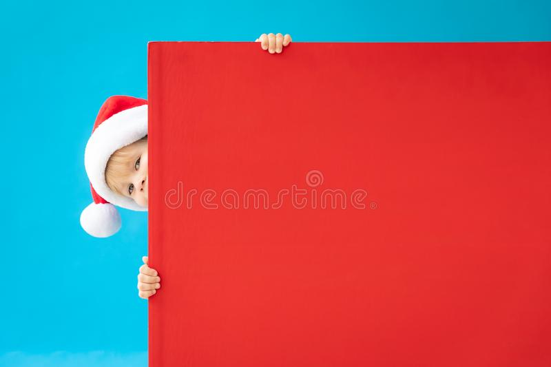 Happy child holding red Christmas banner blank against blue background. Happy child holding red banner blank against blue background. Christmas greeting card royalty free stock photography